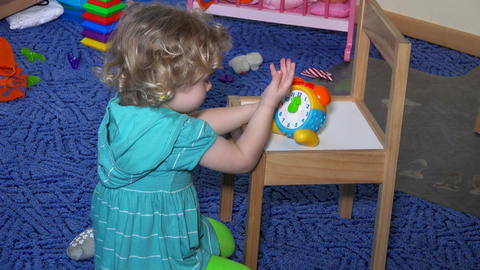 little child playing with toy watch. Learning time for toy manual clock Live Action