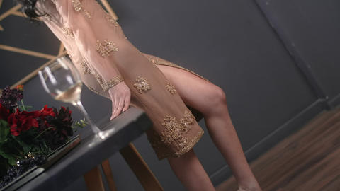 Sexy woman in night dress bends her leg through the cutout, attractive woman Live Action