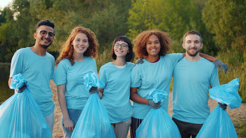 Joyful friends eco activists holding garbage bags standing on river bank hugging Live Action