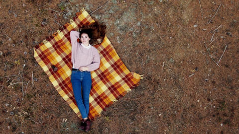 AERIAL: A beautiful young woman lies on a carpet in the middle of the pine GIF