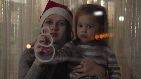 Mom and daughter draw a snowman with paints on a window pane. Drawing with Live Action