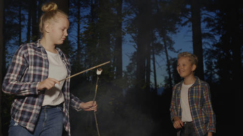 Young girl and boy fried marshmallows on fire in forest hike at evening dinner Live Action