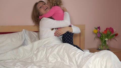 Young mother with 3 years old little daughter are relaxing and playing in bed Live Action