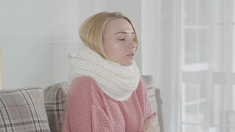 Portrait of young attractive Caucasian woman in white scarf shivering. Blond Live Action