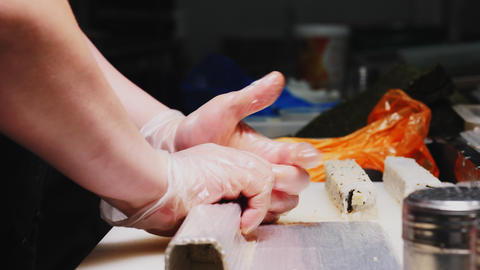 chief in gloves makes tasty sushi roll in kitchen close view Live Action