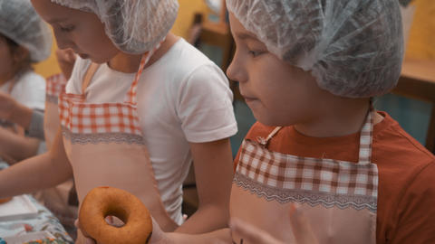 Young boy licking finger while cooking donuts in culinary school. Boy on cooking Live Action