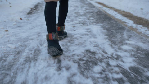 Female legs in black boots dancing in winter path covered snow rear view. Legs Live Action