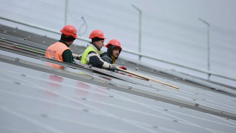 Worker install solar panels Live Action