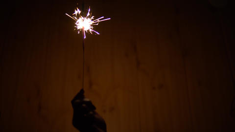 A woman holds a Bengal fire in her hand. Sparklers shine in the dark. Hand with Live Action