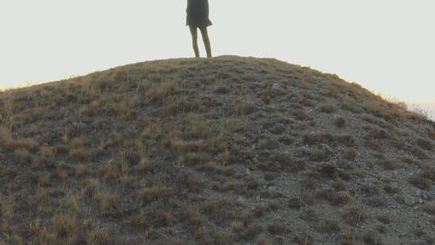 A man in a suit stands on top of a hill and looks at the dawn over the sea GIF