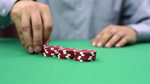 dealer collects red poker chips Live Action