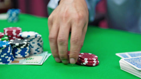 hand collects red poker chips Live Action