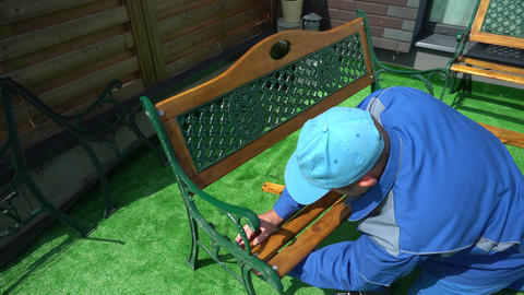 Foreman in blue connect parts of wooden bench in house yard Live Action