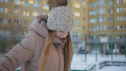 Young girl in winter hat with pompom and down jacket walking in winter city on Live Action