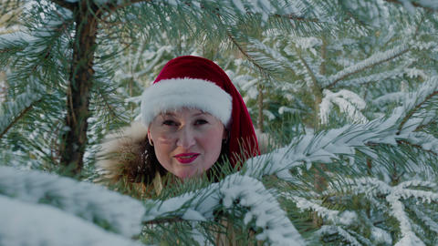 Playful woman in red Christmas hat looking through spruce branch in winter Live Action