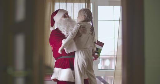 Caucasian man in Santa Claus costume spinning pretty blond Caucasian child Live Action