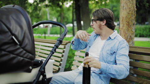 Portrait of attractive man drinks a beer while resting with his newborn baby Live Action