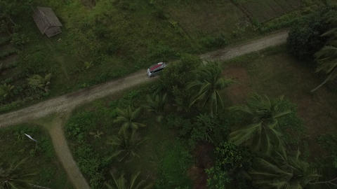 Top view on a car with surfboards on top of it driving on tropical road Live Action