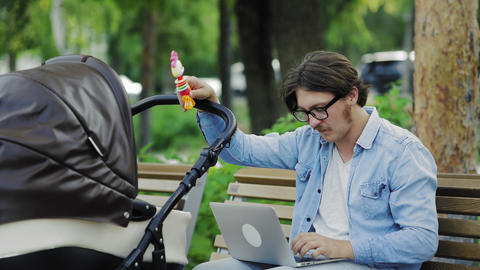 Freelancer sending laptop email and swinging stroller, family and career balance Live Action