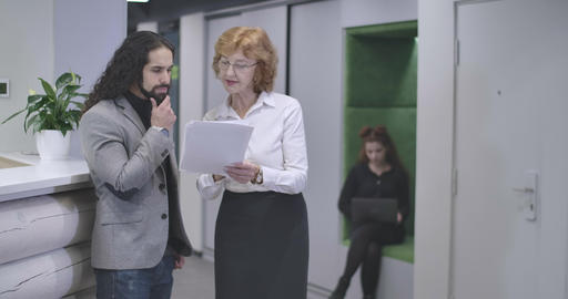 Middle aged Caucasian woman in eyeglasses explaining business project details to Live Action
