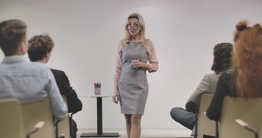 Confident Caucasian adult woman in eyeglasses standing in front of coworkers and Live Action
