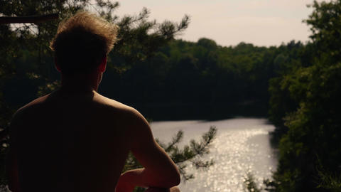 Young Adult sitting on a cliff looking at beautiful lake at sunset in 4k slow motion Live Action