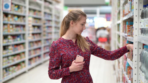 Attractive young woman choosing products in supermarket marketplace Live Action