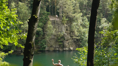 Young Adult swinging into beautiful lake in sunny summer in 4k slow motion Live Action