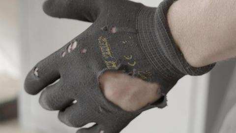 man dressing broken work gloves Live Action