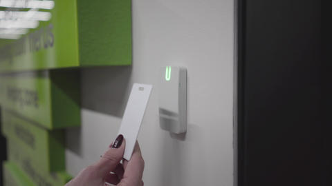 Close-up of closed electronic lock in open space office. Female Caucasian hand Live Action