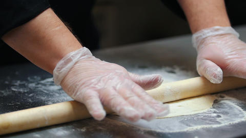 Kitchen - a man making a dough - flatten the dough with a rolling pin Live Action