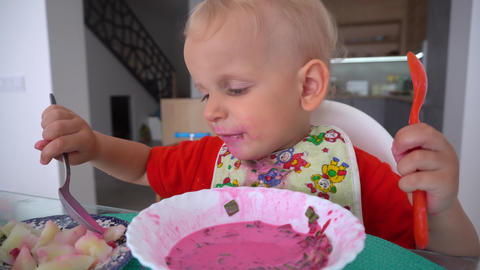 toddler boy eating beetroot soup and potatoes with two spoons. Gimbal movement Live Action
