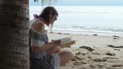 Brunette Woman Reads Book on Sea Coast Live Action