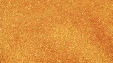 Colorful golden sand organically moves in colorful liquid in macro Live Action