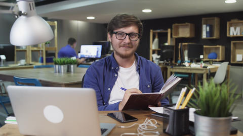 Attractive man with notebook in hand looking at the camera in modern office Live Action