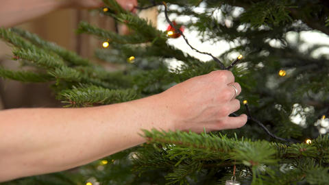 Decorating a Christmas tree shining decorative chains Live Action