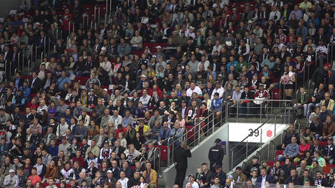 Fans at sporting events closely watching the game of hockey. With sound Footage