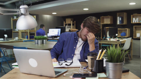 Tired young man sitting at office desktop with laptop and drinking coffee Live Action
