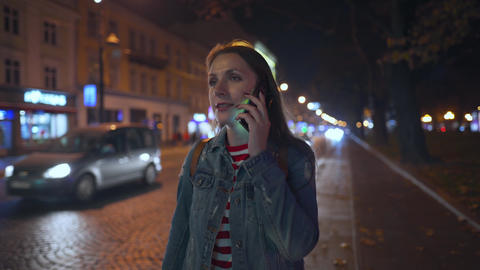 Woman talking on the smartphone while walking through the streets of the evening Live Action