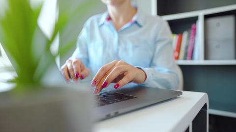 Female hands with bright manicure typing on a laptop keyboard Live Action