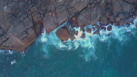 camera rises above cliff near calm ocean aerial view Live Action