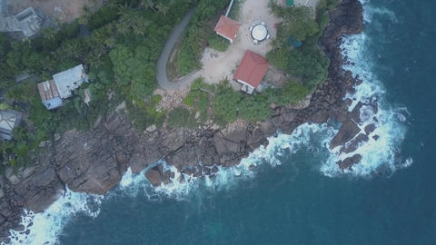 camera rises above hotel on steepy cliff near calm ocean Live Action