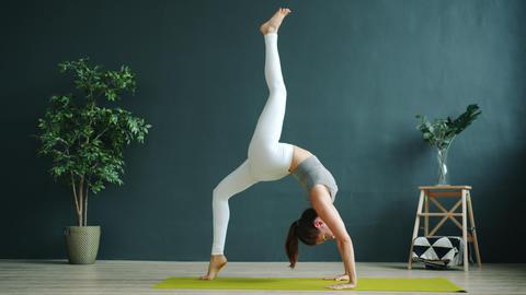 Yoga student exercising alone in modern wellness center doing Chakrasana Live Action