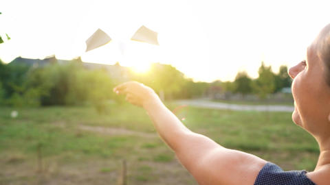 Woman launches paper airplane against sunset background. Dreaming of traveling Live Action