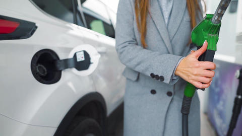 Woman fills petrol into her car at a gas station close-up. Slow motion Live Action