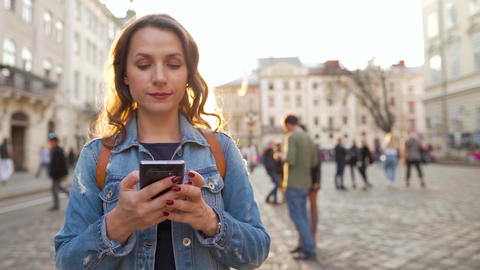 Woman walking down an old street using smartphone at sunset. Communication Live Action