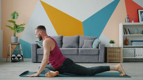 Bearded guy practising yoga in house on mat working out in apartment alone Live Action