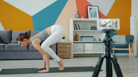 Yoga instructor vlogger making video for online vlog using smartphone camera Live Action