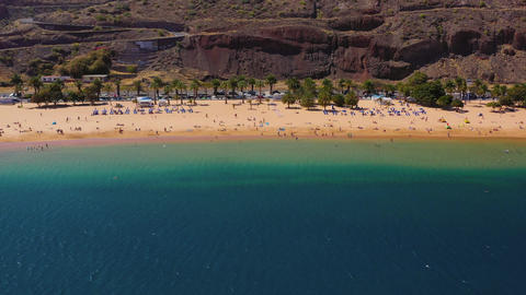 Aerial view of Las Teresitas beach, road, cars in the parking lot, golden sand Live Action