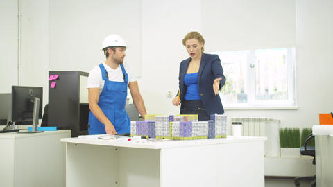 Builder and woman discuss project of houses, they rearrange houses on table Live Action